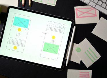 UI website creative designer workspace with template framework for mobile phone layout on dark leather desk